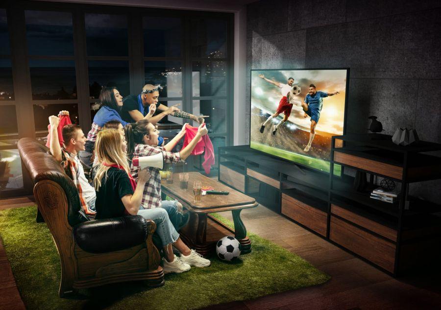 Gruppo di amici che guardare una partita di calcio, lo sport insieme sulla miglior TV 4k