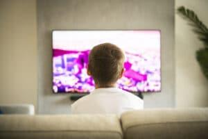ragazzo guarda la tv oled da divano